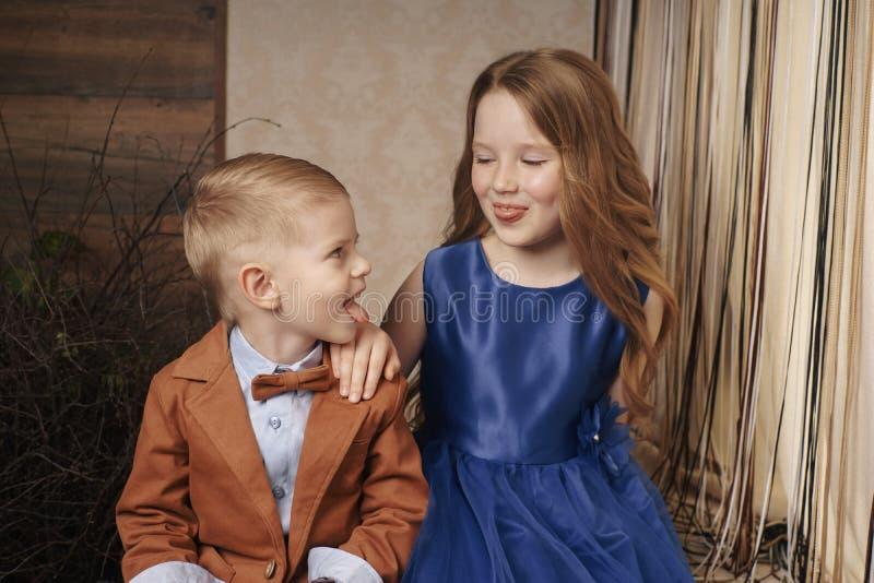 Pequeña muchacha linda del muchacho que abraza jugar en el fondo blanco, cierre feliz de la familia para arriba aislado Sonrisa d fotos de archivo libres de regalías