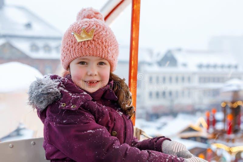 Pequeña muchacha linda del niño que se divierte en la noria en mercado alemán tradicional de la Navidad durante las nevadas fuert imagen de archivo libre de regalías