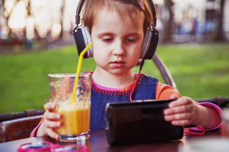 Pequeña muchacha linda del niño que usa el teléfono móvil que mira el vídeo en línea del aprendizaje electrónico a estudiar foto de archivo libre de regalías