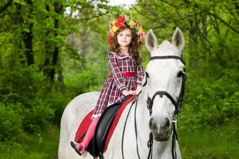 Pequeña muchacha linda en guirnalda floral imagen de archivo