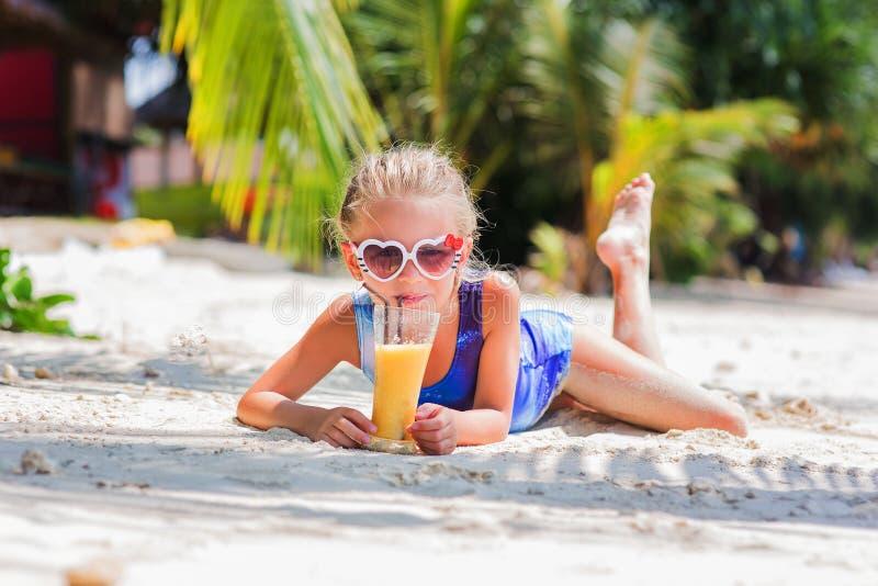 Pequeña muchacha linda en la arena en la playa en vidrios de sol con un vidrio de jugo exótico del cóctel imagen de archivo