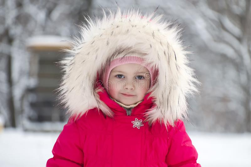 Pequeña muchacha linda en una capilla grande de la piel en invierno fotografía de archivo libre de regalías