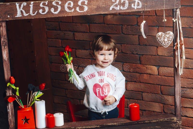 Pequeña muchacha linda feliz con las flores en manos en casa fotos de archivo libres de regalías