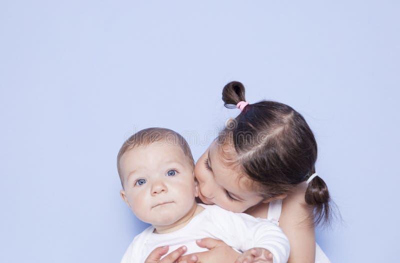Pequeña muchacha linda que abraza al pequeño hermano del bebé fotos de archivo libres de regalías
