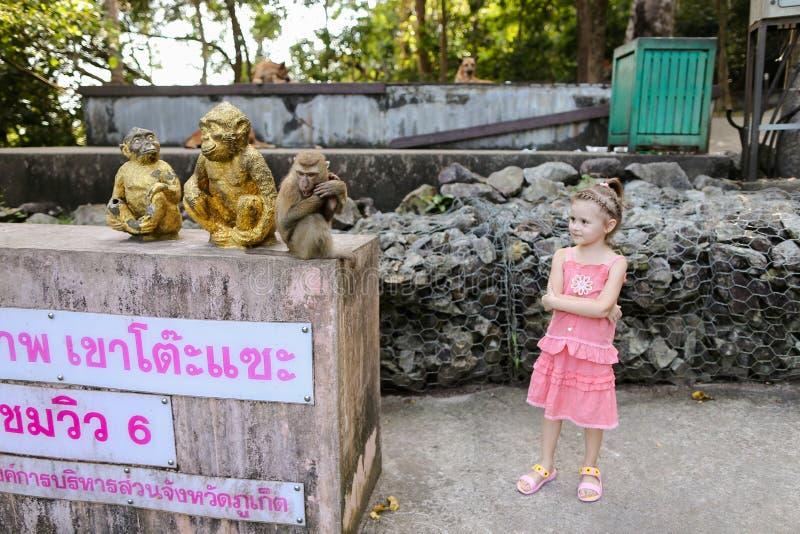 Pequeña muchacha linda que coloca las figurillas de oro y macaco del mono cercano en el parque zoológico en Tailandia imagenes de archivo