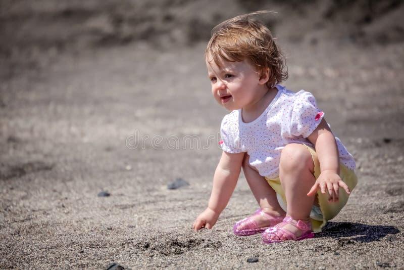 Pequeña muchacha linda que juega en la arena imagenes de archivo