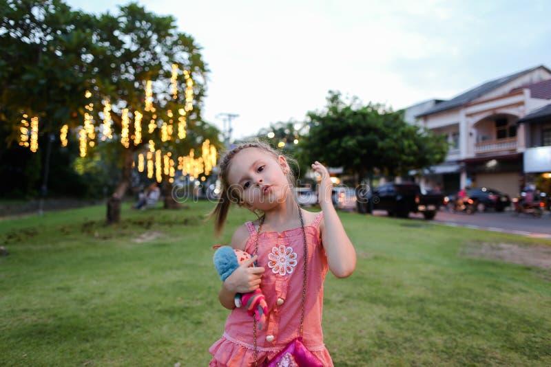 Pequeña muchacha linda que lleva el vestido rosado con el juguete que se coloca en césped en ciudad imágenes de archivo libres de regalías