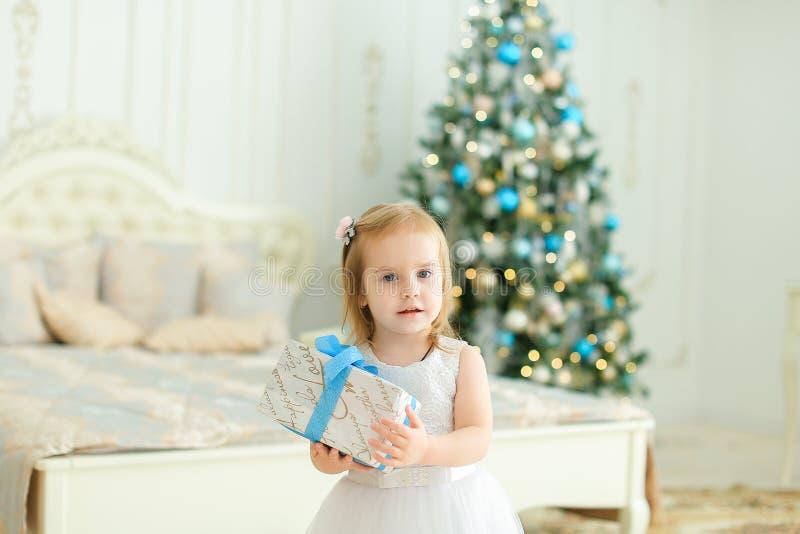 Pequeña muchacha linda que mantiene el presente, el vestido blanco que lleva y la situación dormitorio con el árbol de navidad imágenes de archivo libres de regalías