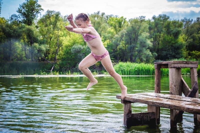 Pequeña muchacha linda que salta del muelle en un río hermoso en la puesta del sol foto de archivo