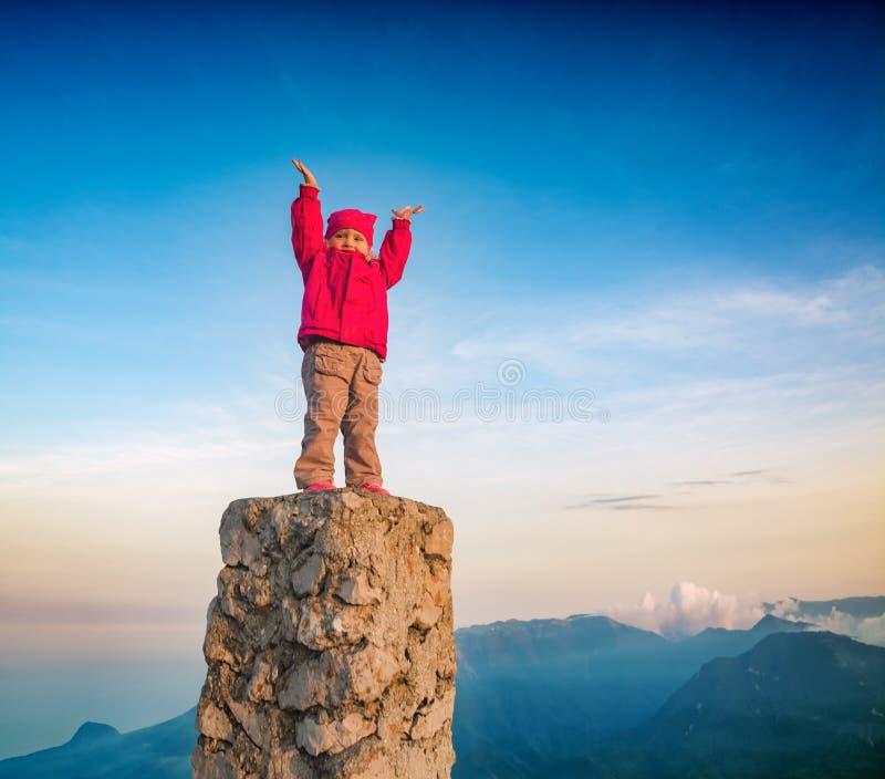 Pequeña muchacha linda que se coloca en un top sobre el valle de la montaña imagen de archivo libre de regalías