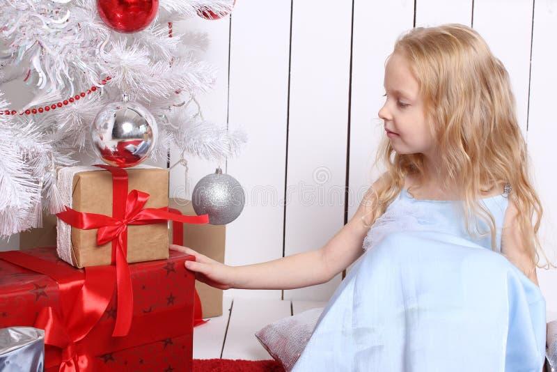 Pequeña muchacha linda que se sienta debajo del árbol y de las cajas de los controles con los regalos fotografía de archivo