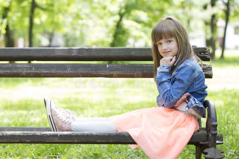 Pequeña muchacha linda que se sienta en un banco y que mira pensativamente imagen de archivo