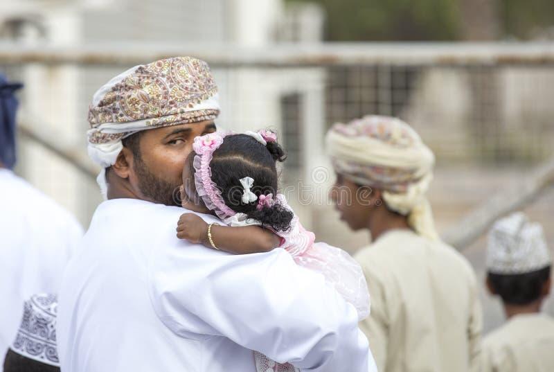 Pequeña muchacha omaní isleeping en un hombro de su papá fotos de archivo libres de regalías