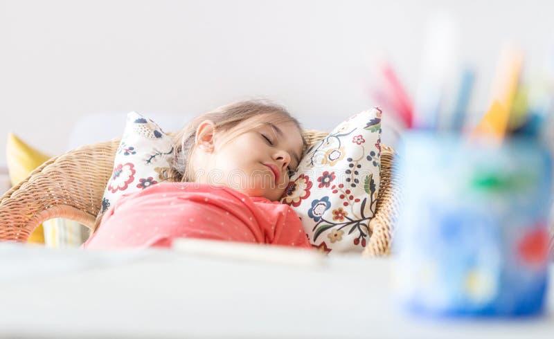 Pequeña muchacha preescolar cansada que duerme en silla cómoda cerca del escritorio foto de archivo libre de regalías