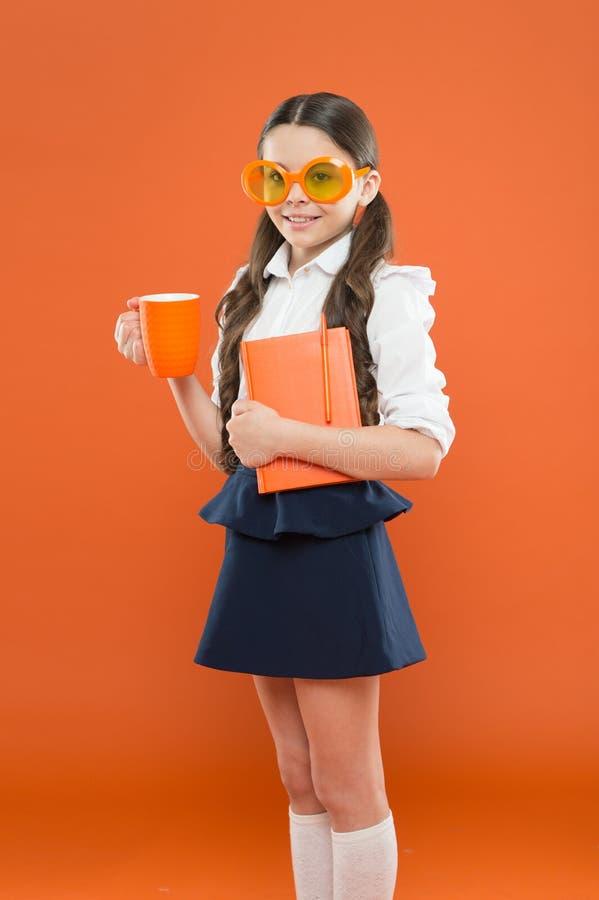 Pequeña muchacha que disfruta de su tiempo de la escuela Pequeña colegiala feliz lista para la lección Niño lindo con el libro Es fotos de archivo