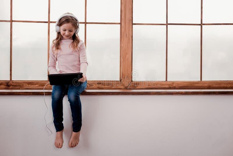Pequeña muchacha que escucha la música imágenes de archivo libres de regalías