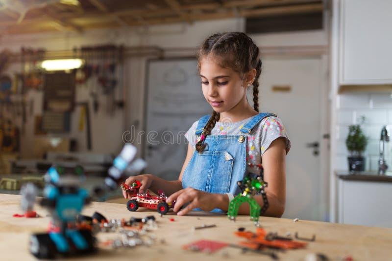 Pequeña muchacha que hace un robot imágenes de archivo libres de regalías