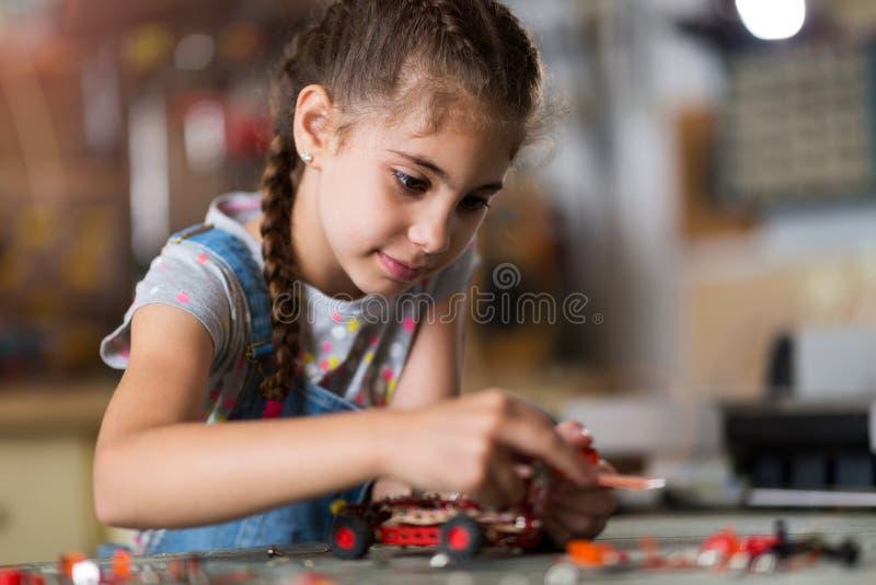 Pequeña muchacha que hace un robot imagen de archivo libre de regalías