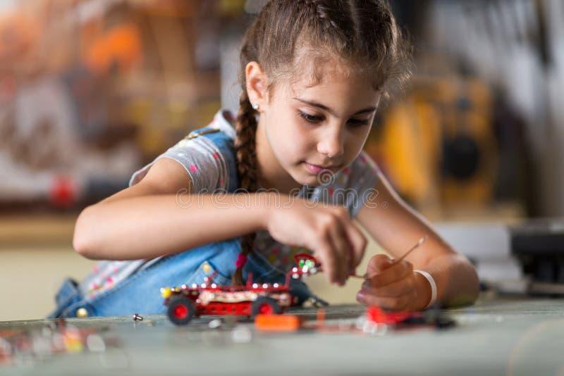 Pequeña muchacha que hace un robot fotografía de archivo