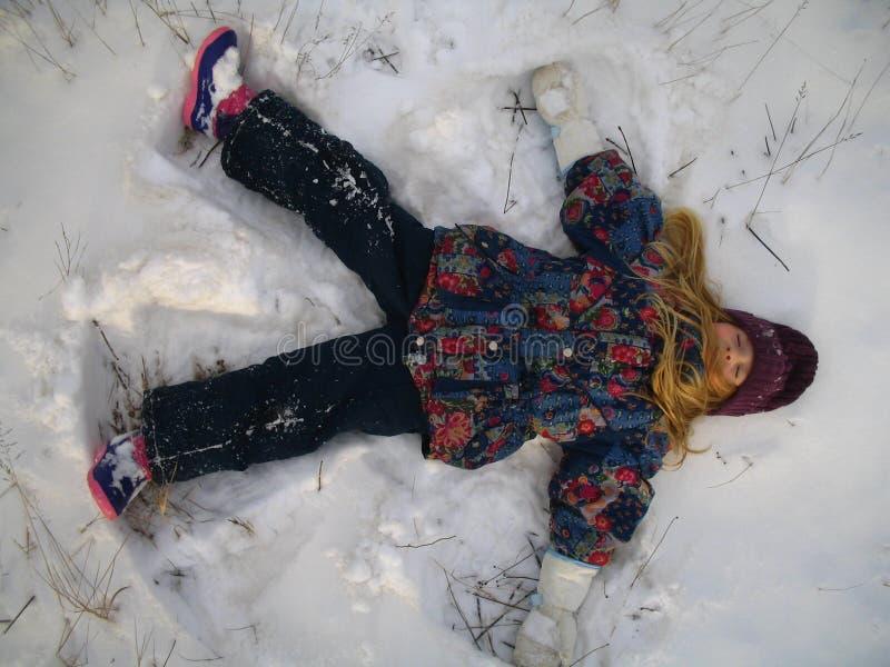 Pequeña muchacha que juega ángel de la nieve imagenes de archivo
