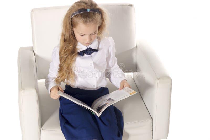 Pequeña muchacha que lee un libro y que se sienta en la silla Colegiala aislada en el fondo blanco Visión superior fotos de archivo libres de regalías