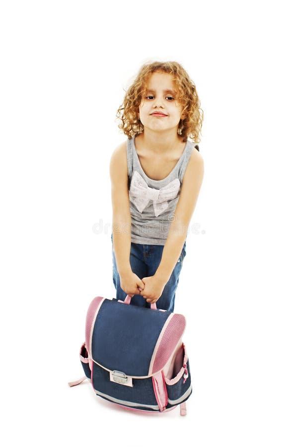 Pequeña muchacha que lleva el bolso de escuela pesado fotos de archivo