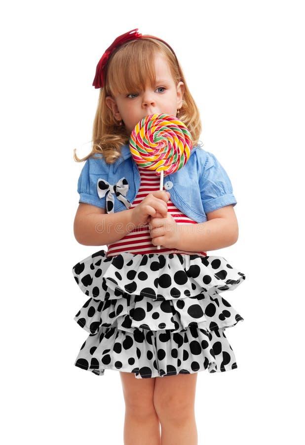 Pequeña muchacha que se coloca con el lollipop fotografía de archivo libre de regalías