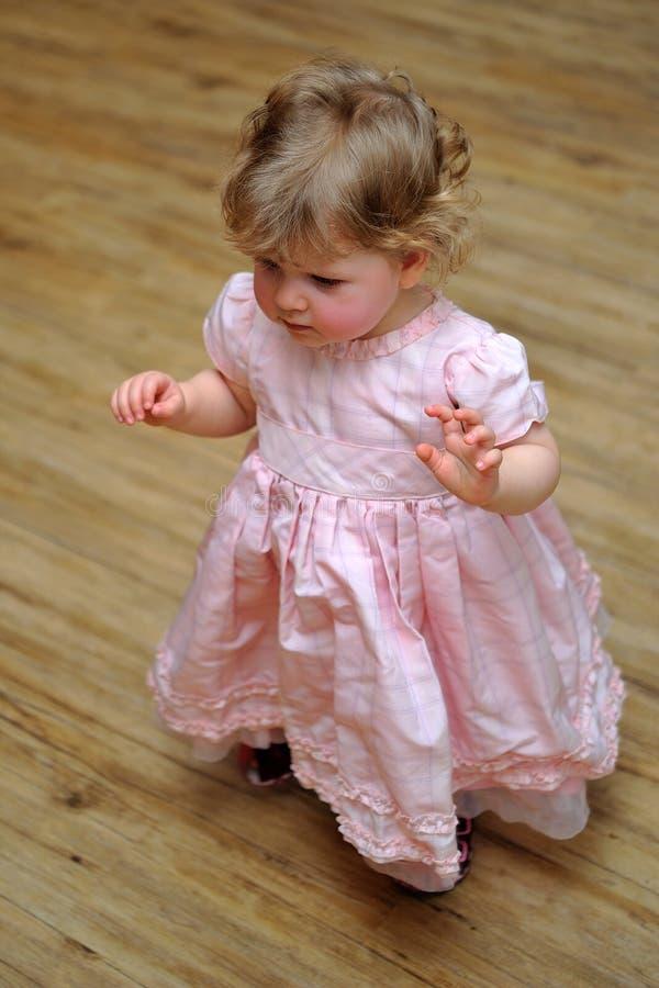 Pequeña muchacha que se coloca en alineada rosada en suelo de madera foto de archivo