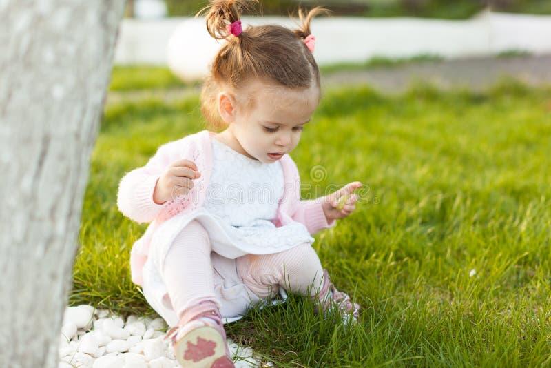 Pequeña muchacha rizada con dos colas que se sientan en un césped cerca de un árbol fotos de archivo libres de regalías