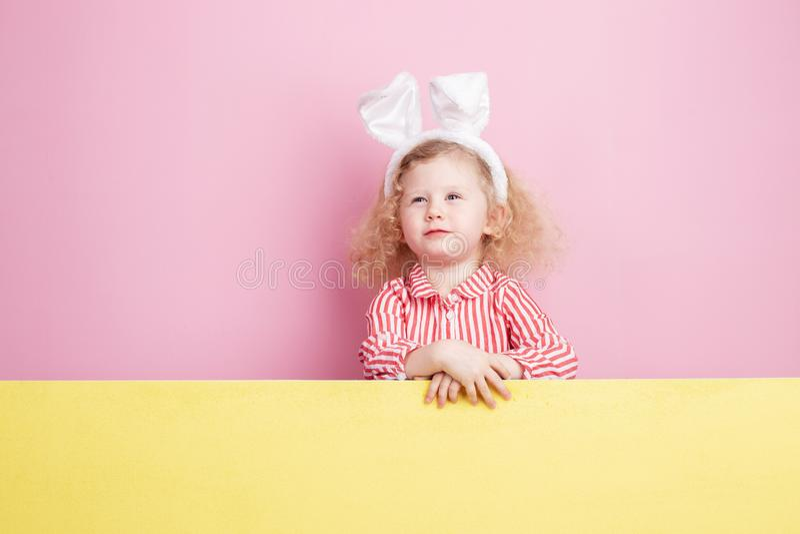 Pequeña muchacha rizada divertida en oídos rojos y blancos rayados del vestido y del conejito en sus soportes principales detrás  imagen de archivo libre de regalías