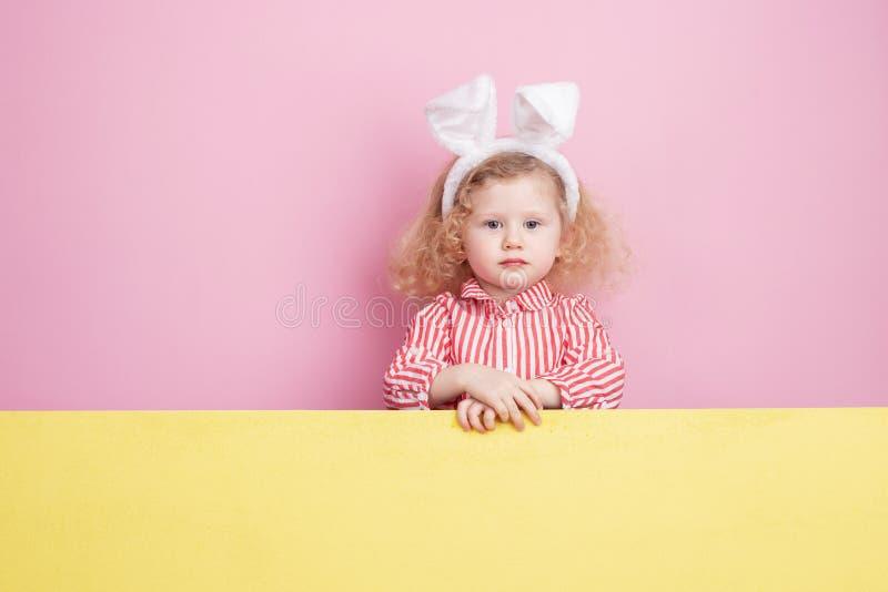 Pequeña muchacha rizada divertida en oídos rojos y blancos rayados del vestido y del conejito en sus soportes principales detrás  fotografía de archivo