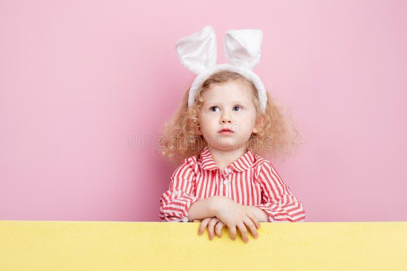 Pequeña muchacha rizada divertida en oídos rojos y blancos rayados del vestido y del conejito en sus soportes principales detrás  foto de archivo