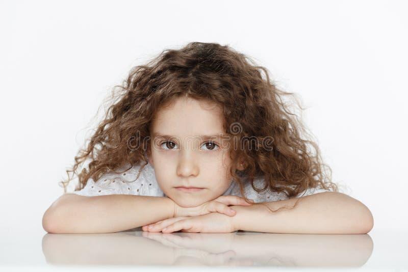 Pequeña muchacha rizada infeliz en blanco asentada en una tabla, aislada en un fondo blanco, mirando la cámara fotografía de archivo libre de regalías
