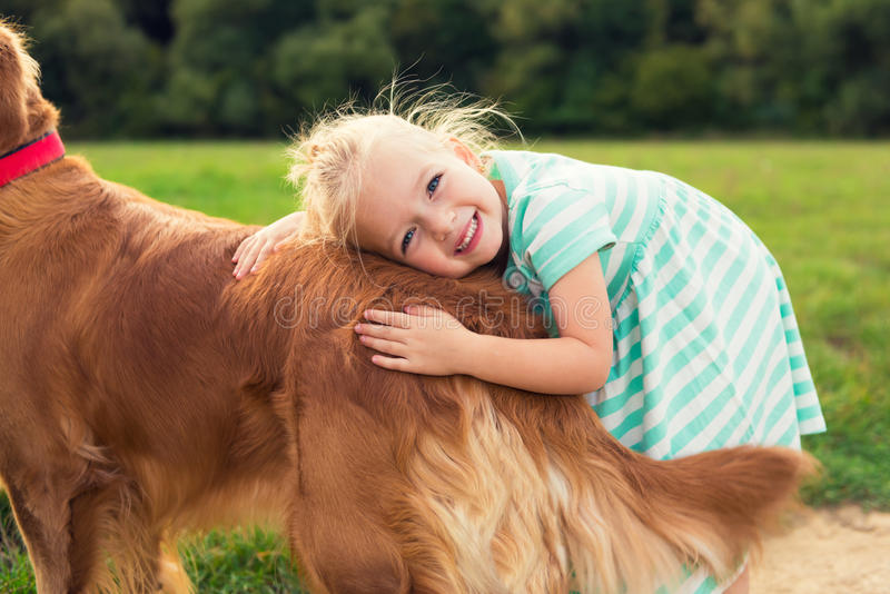 Pequeña muchacha rubia adorable que abraza su perro imagen de archivo
