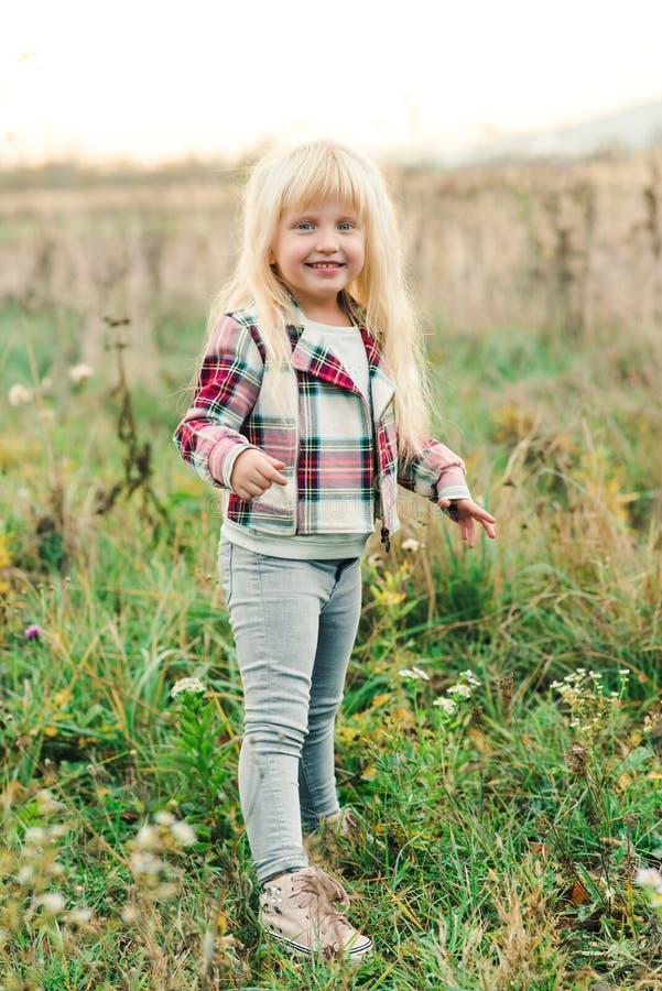 Pequeña muchacha rubia adorable que ríe en un prado Niño feliz en un paseo del verano Muchacha elegante que se divierte en un rat imagen de archivo