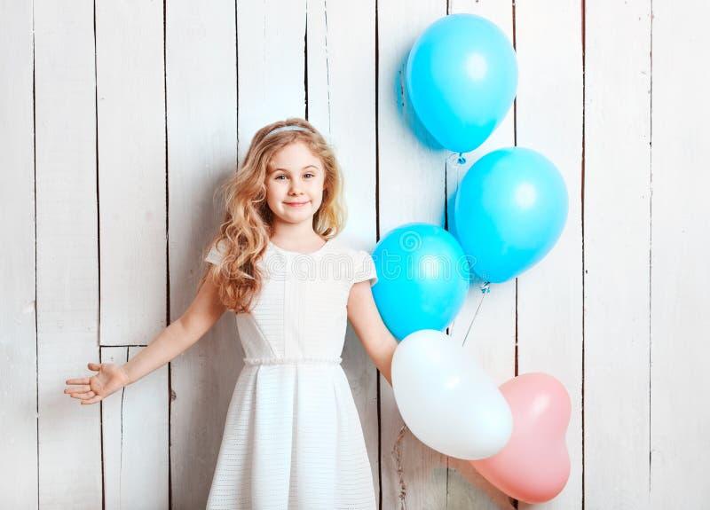 Pequeña muchacha rubia alegre con los globos en el backgrou de madera blanco fotografía de archivo