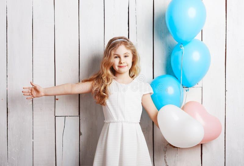 Pequeña muchacha rubia alegre con los globos en el backgrou de madera blanco fotos de archivo