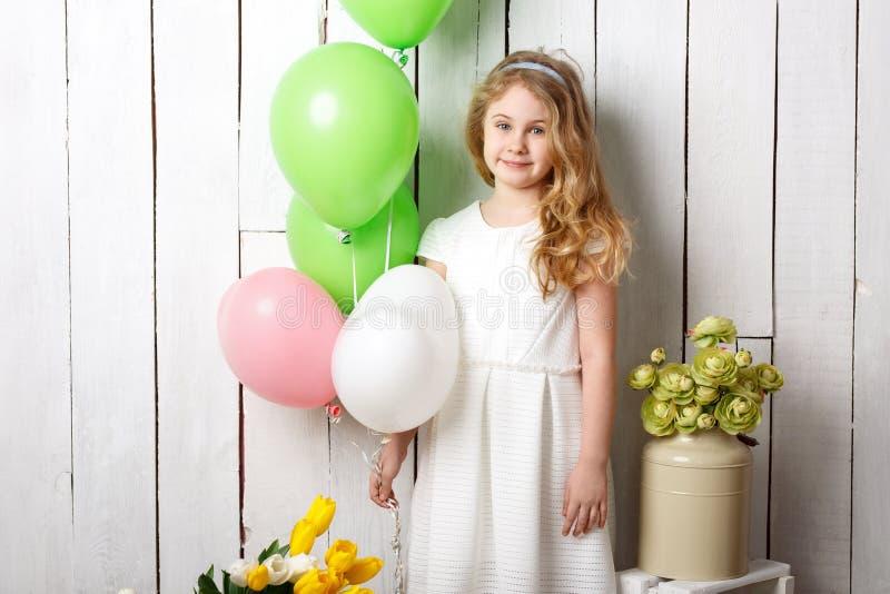 Pequeña muchacha rubia alegre con los globos en el fondo de madera blanco imagen de archivo