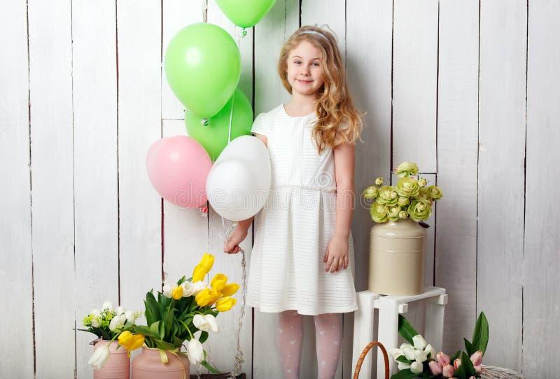 Pequeña muchacha rubia alegre con los globos en el fondo de madera blanco foto de archivo libre de regalías