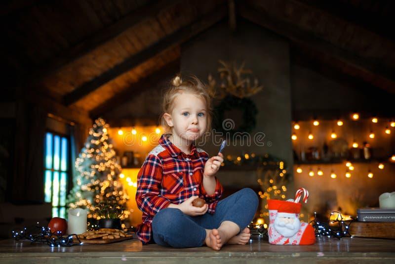 Pequeña muchacha rubia blanca que se sienta en una tabla de madera en la sala de estar del Chale imagen de archivo