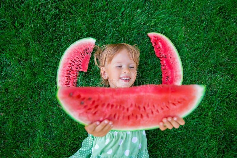 Pequeña muchacha rubia feliz que miente en la hierba con la sandía grande de la rebanada en tiempo de verano Sonrisa Visión super foto de archivo