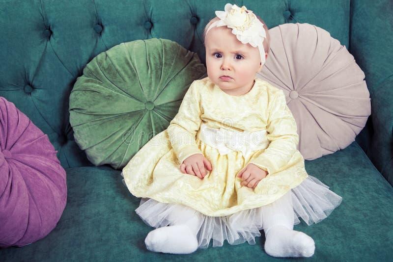 Pequeña muchacha rubia hermosa con el vestido y la flor amarillos en su cabeza imagenes de archivo