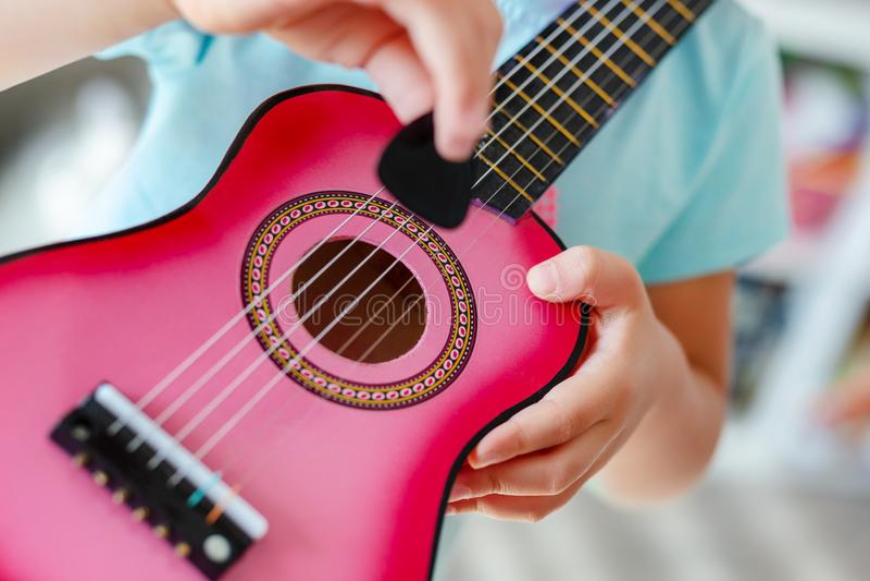 Pequeña muchacha rubia linda del primer que se divierte que aprende tocar la pequeña guitarra del ukelele en casa Niña pequeña qu imagenes de archivo