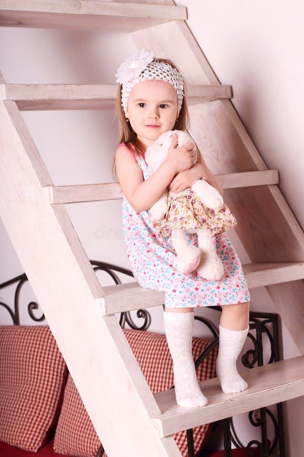 Pequeña muchacha rubia linda en el vestido que se sienta en las escaleras de madera con tan imagen de archivo