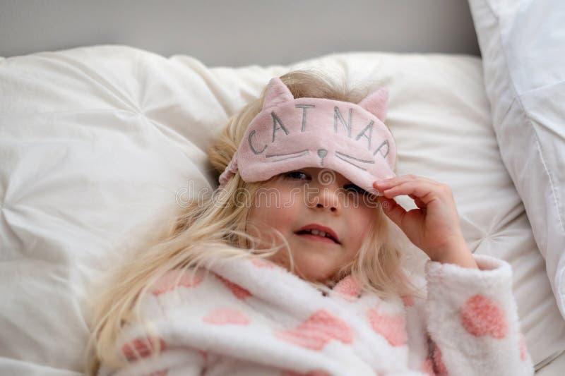 Pequeña muchacha rubia linda que consigue lista para la siesta foto de archivo