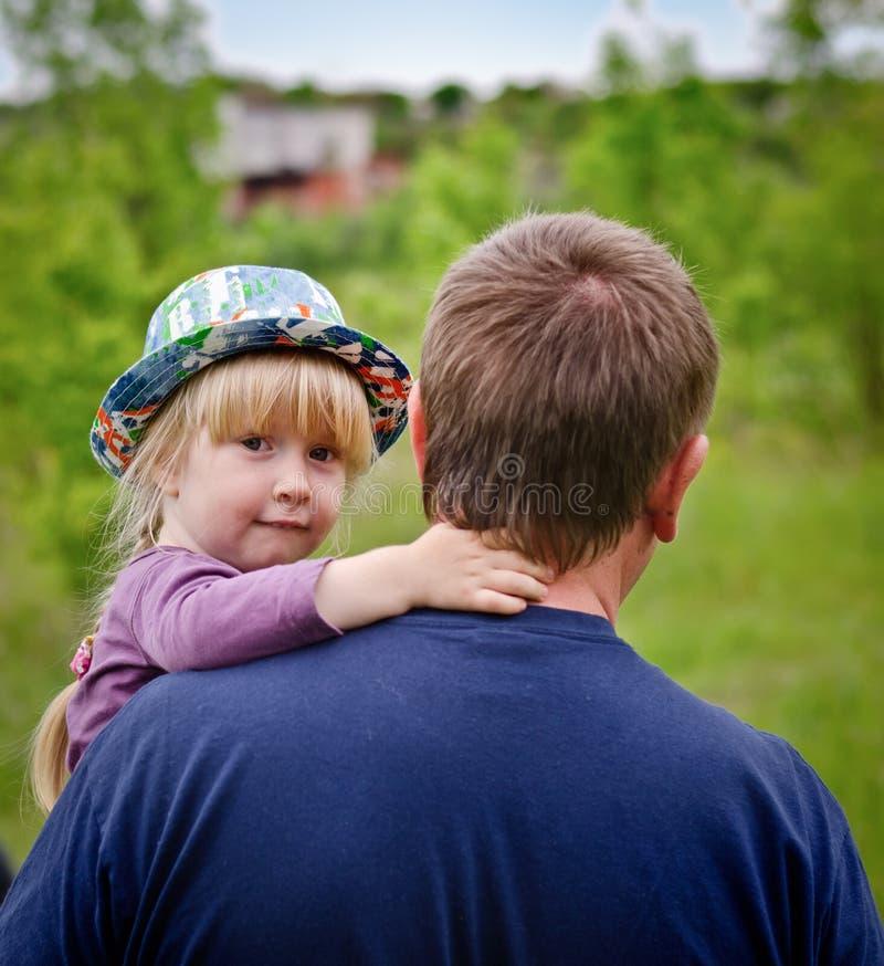 Pequeña muchacha rubia linda que es llevada por su padre imagen de archivo libre de regalías