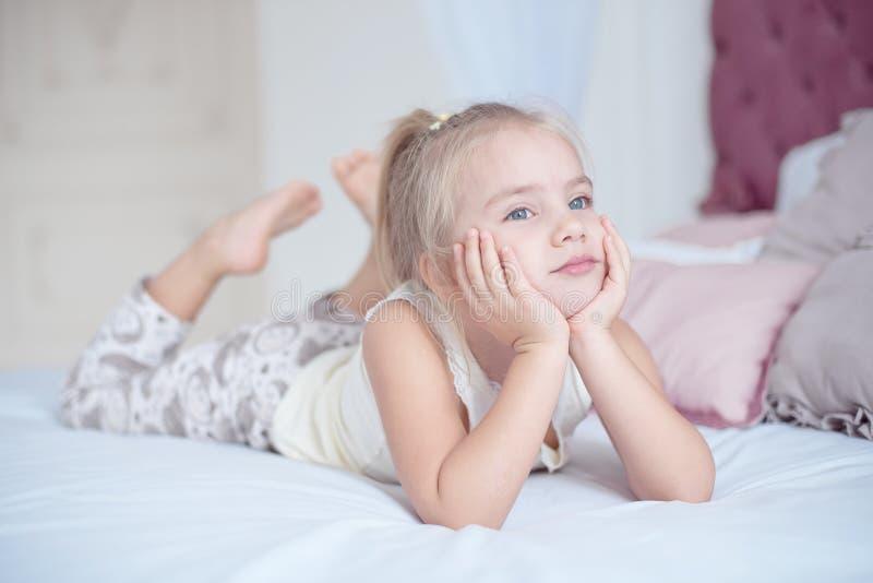 Pequeña muchacha rubia linda que miente en cama foto de archivo