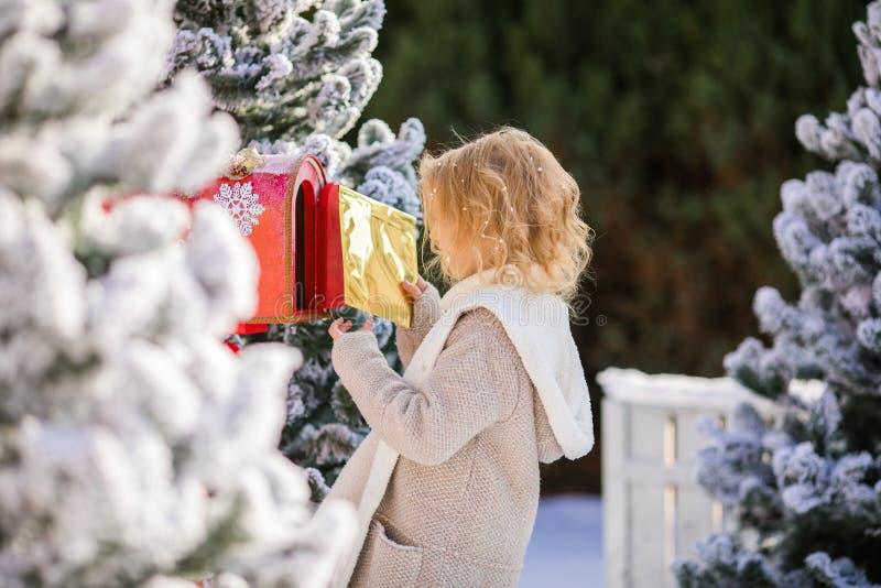 Pequeña muchacha rubia que envía su letra con el wishlist a Papá Noel, tiempo de la Navidad imagen de archivo libre de regalías