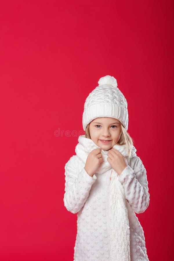Pequeña muchacha rubia sonriente en un sombrero y una bufanda blancos en backg rojo foto de archivo