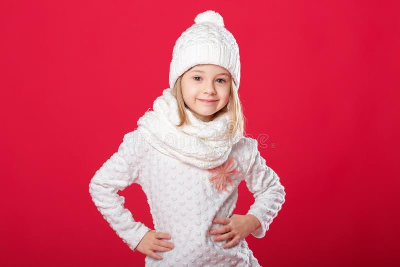 Pequeña muchacha rubia sonriente en un sombrero y una bufanda blancos en backg rojo imagen de archivo